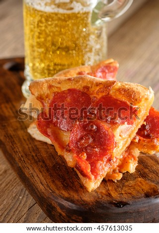 Pepperoni Pizza slice on wooden background. Italian cuisine. - stock photo