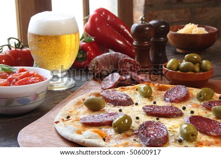 Pepperoni pizza, with a glass of beer and ingredients - stock photo