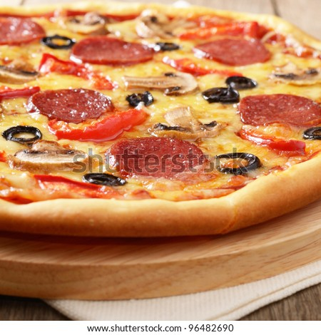 Pepperoni pizza with mushrooms and peppers - stock photo