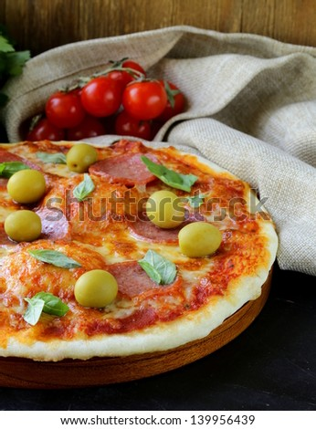 Pepperoni pizza with tomato sauce and herbs on a wooden board