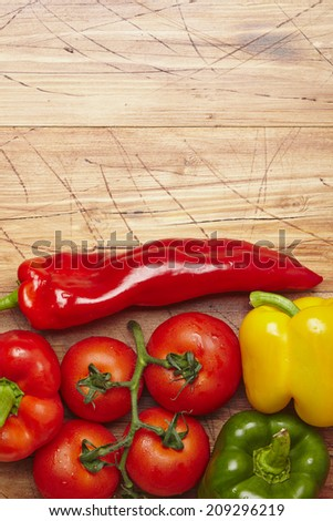 peppers and tomatoes on a wooden table - stock photo
