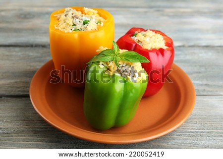 Peppers prepared for cooking stuffed paprika with meat and rice, on plate, on wooden background - stock photo