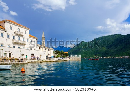 PERAST, MONTENEGRO - JUNE 28, 2015: Scene of the promenade, with local church and other buildings, locals and tourists, in Perast, Montenegro