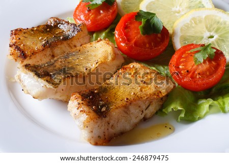 perch fried fillet on a plate with vegetables. Horizontal close-up  - stock photo