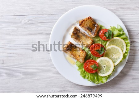 perch fried fillet on a plate with vegetables. horizontal view from above  - stock photo