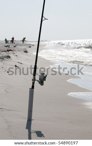 PERDIDO KEY, FL - JUNE 9: A fishing pole on the beach of the Gulf of Mexico as BP oil spill workers (background) clean the seashore on June 9, 2010 as oil threatens beaches near Pensacola, FL. - stock photo