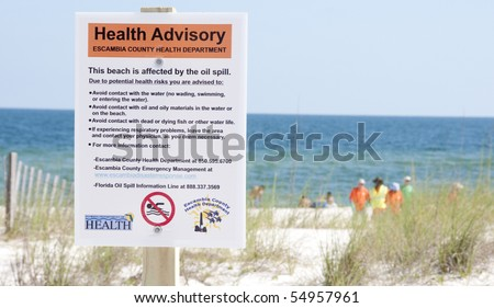 PERDIDO KEY, FL - JUNE 10:  A warning sign is posted at the beach as the oil washes ashore on June 10, 2010 in Perdido Key, FL.  Oil spill workers can be seen in the distance. - stock photo