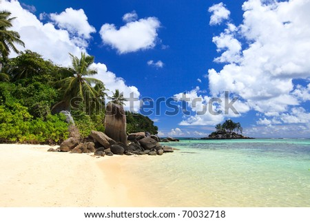 Perfect beach in Seychelles with white sand, turquoise waters, palm trees and blue sky