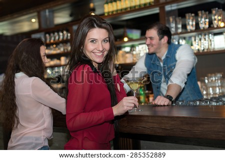 Perfect beer evening in a pub. Portrait of beautiful girl in a pub. Girls is holding alcohol cocktail. Barman is on the background. Beer pub concept