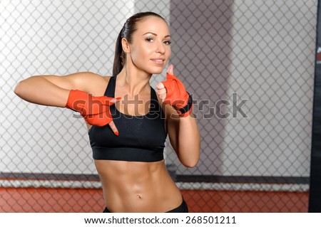 Perfect body. Attractive young sports woman showing her thumb up standing in a fighting cage - stock photo