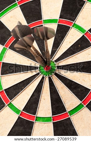 Perfect bulls-eye dart throw on a colorful dartboard.