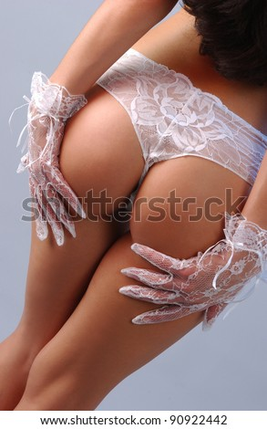 perfect buttocks of elegant brunette woman in white sexy lingerie and gloves on isolated grey background. - stock photo