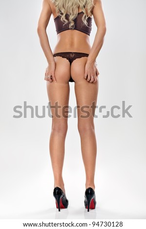 perfect buttocks of elegant  woman in  sexy lingerie on  grey background. - stock photo