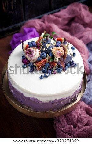 Perfect cake decorated with blueberries, figs, dry roses, edible gold and dry sugar violas. Stylized with cheesecloth. Natural light. - stock photo