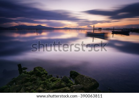 Perfect calm lagoon creates amazing reflection at sunset with a fisherman boat - long exposure - stock photo