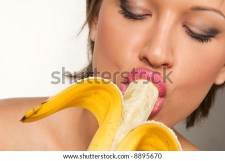 Perfect caucasian young model eating yellow banana - stock photo