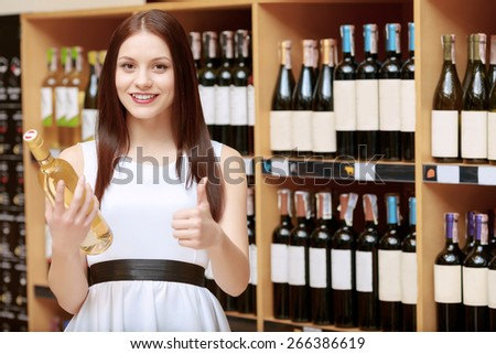Perfect choice. Young smiling woman holding a wine bottle and showing thumb up in a liquor store - stock photo