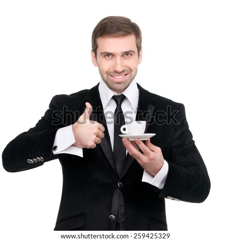 Perfect coffee. Handsome smiling businessman holding a cup of coffee. Thumbs up. Isolated - stock photo