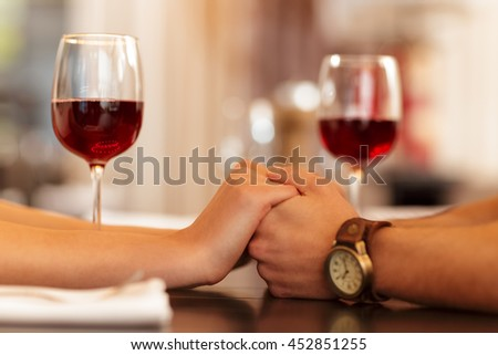 Perfect date. Cropped closeup of a loving couple holding hands wine glasses on the background