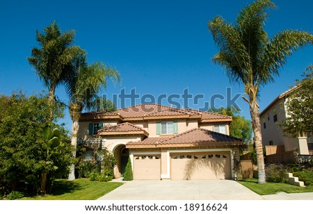 Perfect Dream House with Tile Roof Framed by Palm Trees and Blue Sky