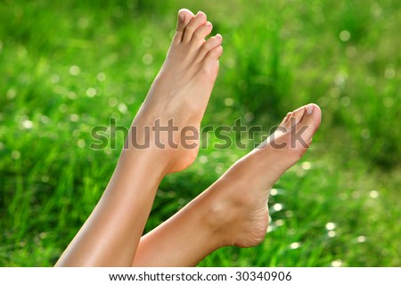 Perfect Feet in the sun with shaved legs on a meadow of a young sexy woman or girl - stock photo