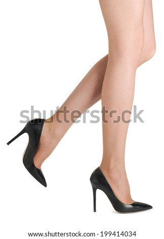 Perfect female legs wearing black high heels isolated on white background.