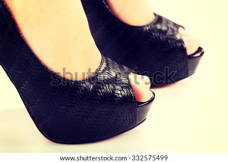 Perfect female legs wearing high heels. - stock photo