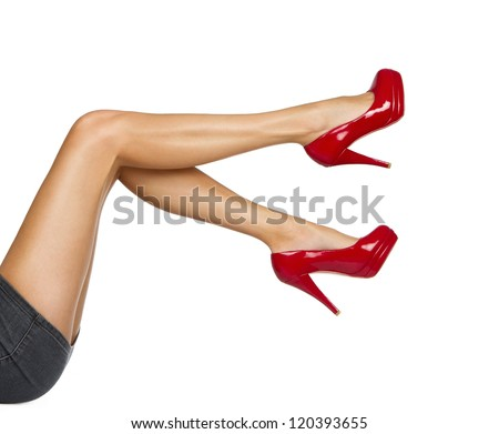 Perfect female legs wearing high heels isolated on white background - stock photo