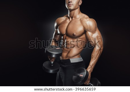 Perfect fit athletic guy workout with dumbbells, perfect abs, shoulders, biceps, triceps and chest.Fitness muscular body isolated on dark background. - stock photo