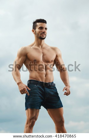 Perfect form. Muscular young man showing off his sculpted body outdoors. - stock photo