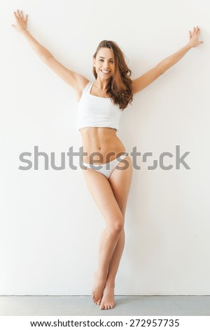 Perfect forms. Full length of attractive young woman in white tank top and panties posing while standing against white background - stock photo