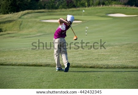 PERFECT GOLF SWING BY A 9 YEARS OLD BOY PLAYING IN JUNIOR LEAGUE GOLF / TEE OFF SHOT WITH DRIVER RIGHT ON MIDDLE OF FAIRWAY / MARYLAND / USA    - stock photo