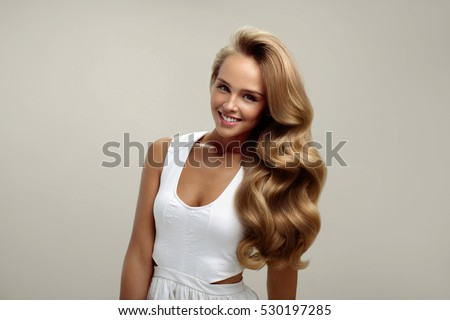 Perfect Hair. Beautiful Smiling Woman Model With Long Shiny Blonde Wavy Curly Hair On White Background. Portrait Of Sexy Girl With Natural Makeup, Beauty Face And Fashion Hairstyle. High Resolution