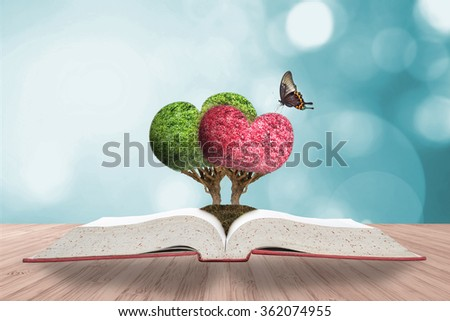 Perfect heart shape tree couple w/ beautiful butterfly growing on good soil planting on story book on wooden table w/ blurred natural background cool color vintage style bokeh: Happy Valentine's day - stock photo