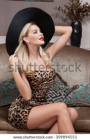 Perfect house.beautiful blond model sitting on couch in leopard print dress with  black hat  his head and a red lipstick in interior.Young woman in black hat sits in a beautiful interior.Elegant woman - stock photo