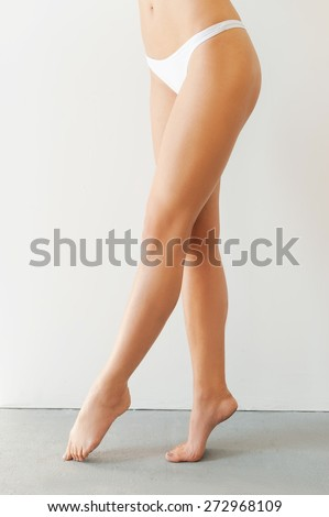 Perfect legs. Cropped image of young woman with long legs standing against white background   - stock photo