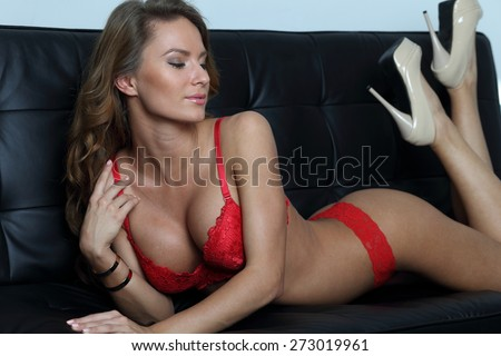 Perfect lingerie model in red on black sofa - stock photo