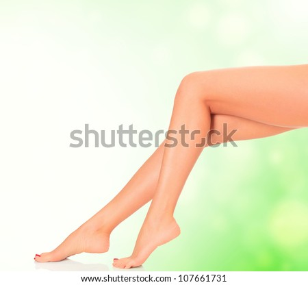 Perfect long female legs on green blurred background. - stock photo