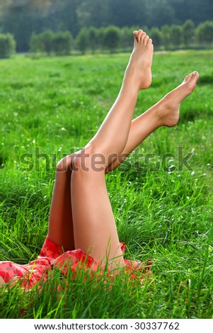 Perfect long legs. Natural Beauty with shaved legs is laying down into the grass on a big meadow pasture.