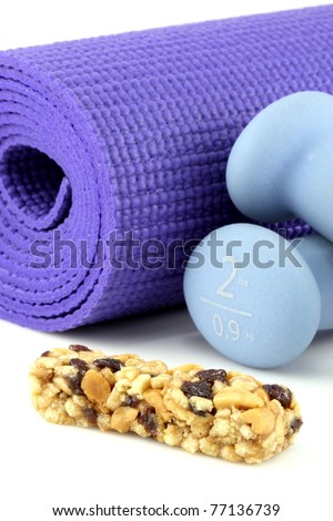 perfect losing weight combo for women, cereal bar with protein,fiber and good carbs plus a yoga mat  and  women dumbbell weights. - stock photo