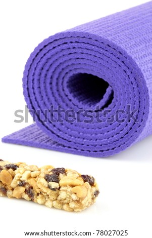 perfect losing weight combo for women, cereal bar with protein,fiber and good carbs plus a yoga mat - stock photo