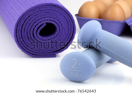 perfect losing weight combo for  women, eggs great source of  protein,yoga mat  and  women dumbbell weights. - stock photo