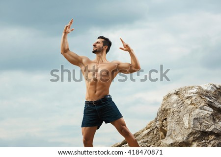 Perfect male form. Shot of a handsome shirtless young man showing his muscles with his hands raised.