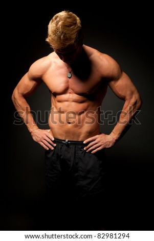 Perfect male half naked in jeans posing,with hands on his hips and looking down to the ground.Dark shadow atmosphere. - stock photo