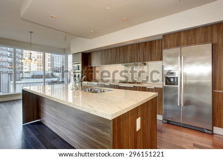 Perfect modern kitchen with hardwood floor and stainless steel fridge. - stock photo