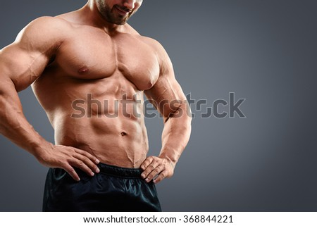 Perfect muscular chest and abs. Cropped image of muscular man standing isolated on grey background