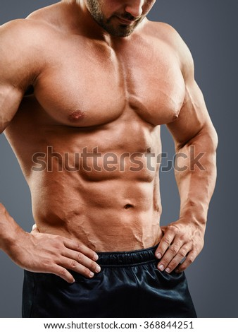 Perfect muscular chest and abs. Cropped image of muscular man standing isolated on grey background - stock photo