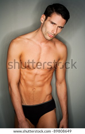 perfect naked male person in small black underwear posing in front of gray background.Ring flash used