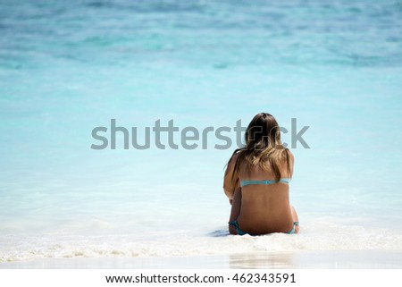 Perfect paradise summer vacation happiness carefree happy woman relaxing sitting in sand enjoying tropical beach destination. Back view of bikini girl on holiday.
