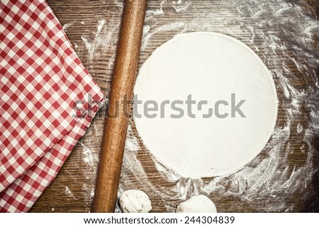 Perfect pizza dough with fresh, bio ingredients and flour on wooden table - stock photo